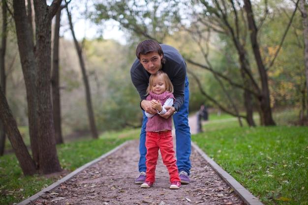 Petite fille avec jeune papa dans le parc au chaud jour d'automne