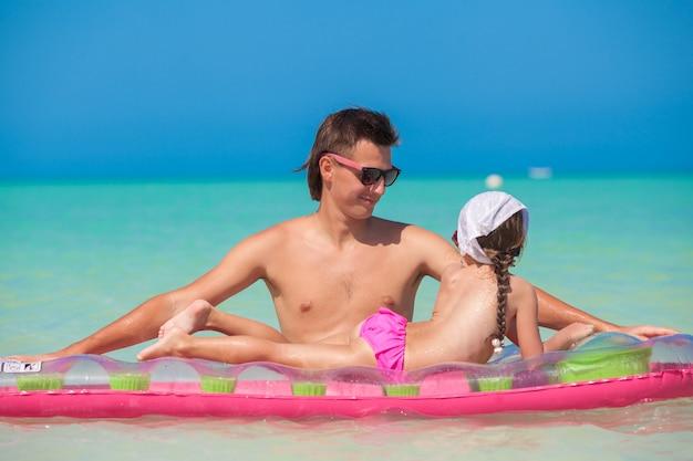 Petite fille avec jeune père sur un matelas pneumatique à la mer