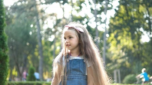 Petite fille jolie enfant marchant à l'extérieur dans le parc d'été vert.