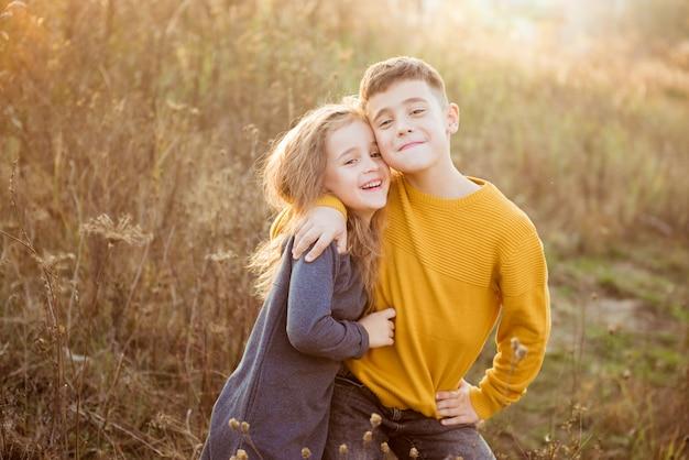 Petite fille jolie et jeune garçon s'embrassant le jour de l'automne. frère et petite soeur câlins. famille heureuse