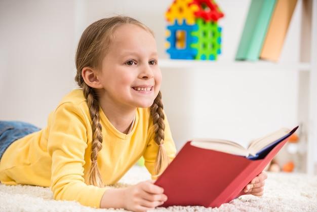 Petite fille jolie en livre de lecture pull jaune.