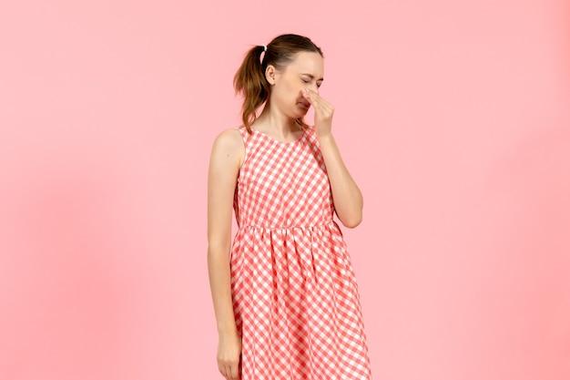 Petite fille en jolie robe lumineuse couvrant son nez rose