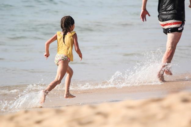 Petite fille jouait pourchasser son père sur la plage.