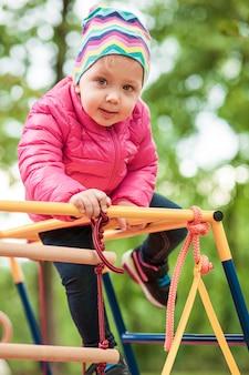 La petite fille jouant à l'aire de jeux extérieure