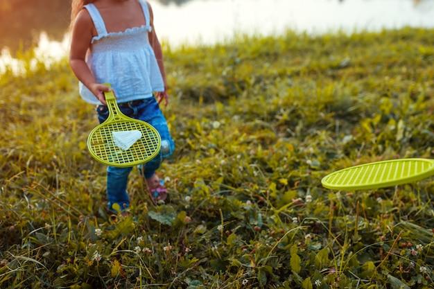 Petite fille jouant au badminton avec soeur dans le parc de l'été