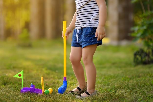 Petite fille jouant au mini golf dans le parc du printemps