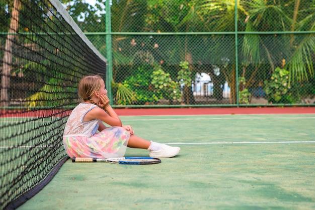Petite fille jouant au tennis sur le court