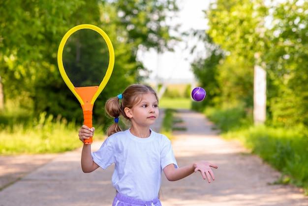 Petite fille jouant au tennis.