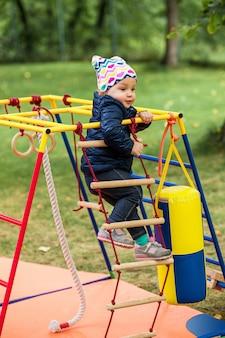 La petite fille jouant au terrain de jeux extérieur