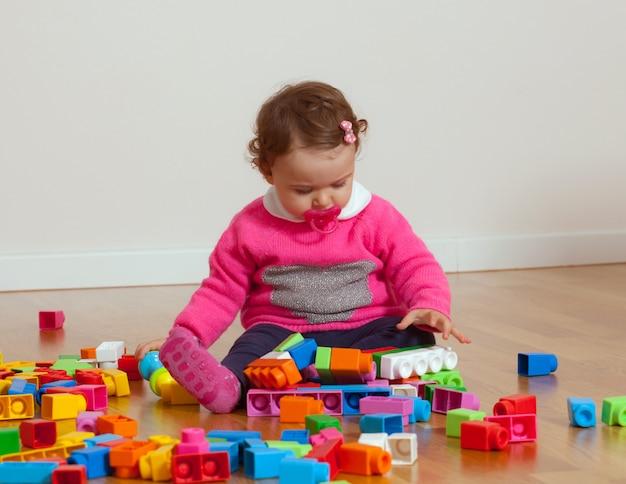 Petite fille jouant avec des blocs de caoutchouc.