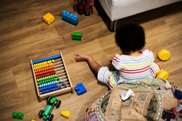 Petite fille jouant avec des blocs de construction sur le sol