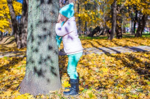 Petite fille jouant à cache-cache près d'un arbre dans un parc en automne