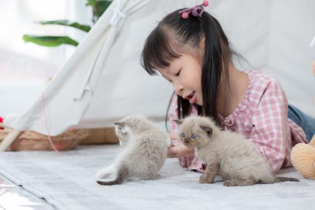 Petite fille jouant avec un chat à la maison, notion de navire ami.