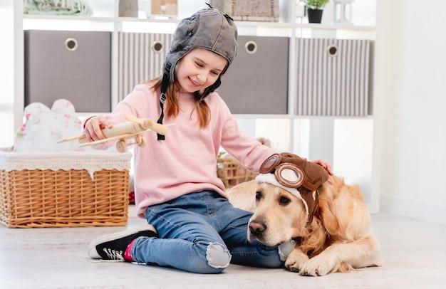 Petite fille jouant avec un chien en bois et golden retriever portant des lunettes de pilote allongé sur le sol