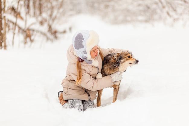 Petite fille jouant avec un chien dans la forêt d'hiver. plaisir d'hiver
