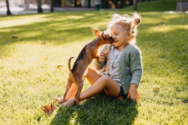 Petite fille jouant avec un chiot à l'extérieur