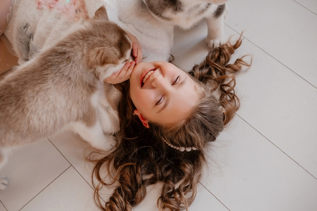 Petite fille jouant avec des chiots husky