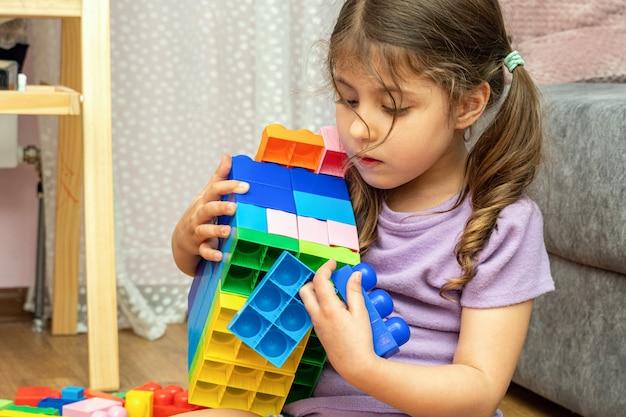 Petite fille jouant avec le constructeur de blocs de jouets éducatifs