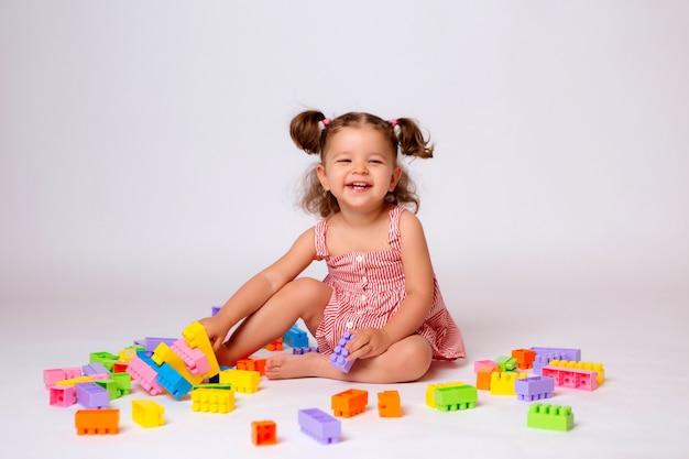Petite fille jouant avec le constructeur multicolore