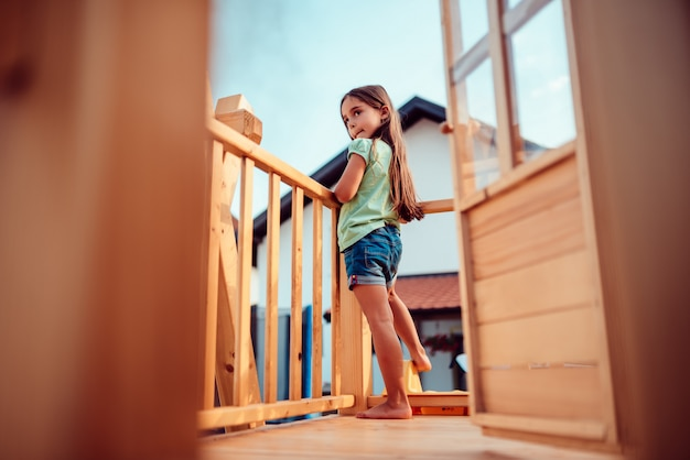 Petite fille jouant dans une cabane dans les arbres en regardant en arrière