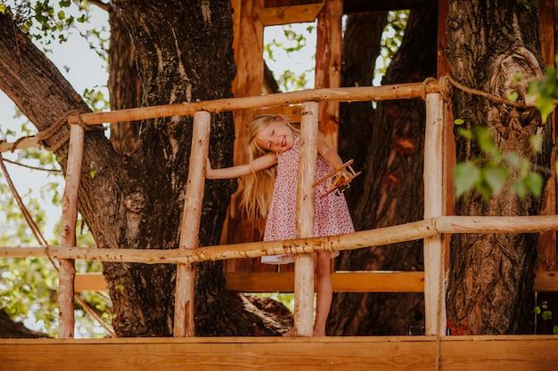 Petite fille jouant dans une cabane dans les arbres
