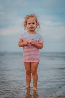 Petite fille jouant dans les vagues en mer