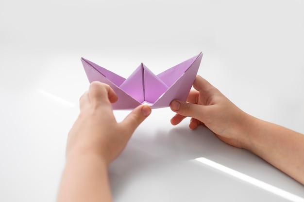 Petite fille jouant avec du papier origami à la maison