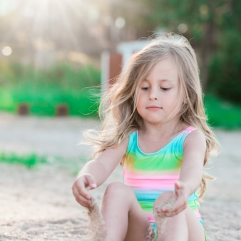 Petite fille jouant avec du sable
