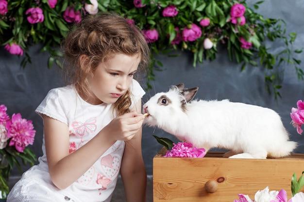 Petite fille jouant avec du vrai lapin. enfant et lapin blanc à pâques. enfant en bas âge nourrissant un animal de compagnie. les enfants et les animaux jouent. amusement et amitié pour les animaux et les enfants.