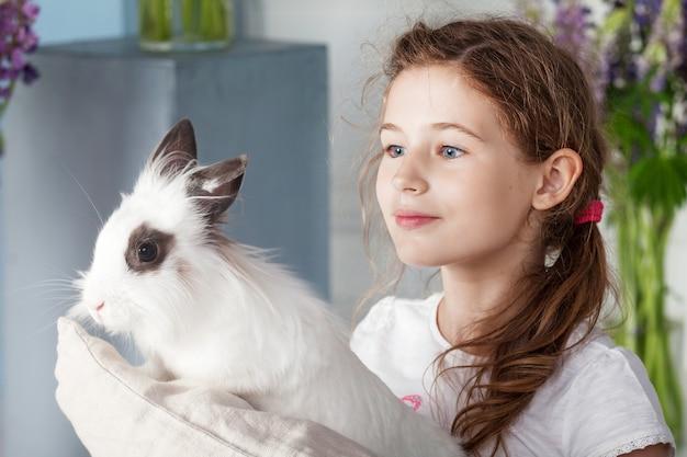 Petite fille jouant avec du vrai lapin. enfant et lapin blanc à pâques. les enfants et les animaux jouent. amusement et amitié pour les animaux et les enfants.