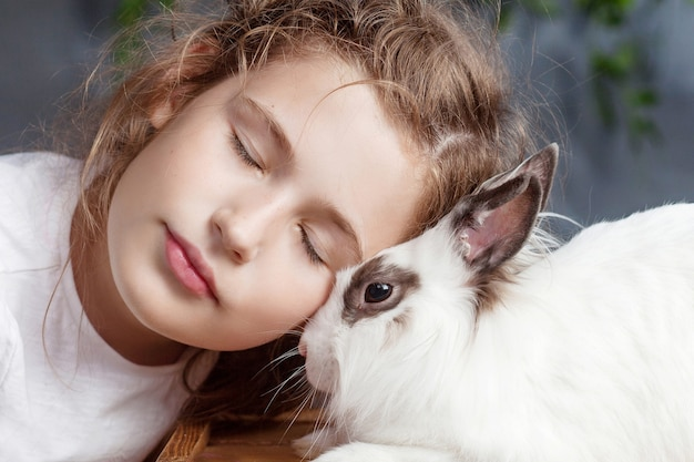Petite fille jouant avec du vrai lapin. enfant et lapin blanc à pâques. kid baiser animal de compagnie. amusement et amitié pour les animaux et les enfants.
