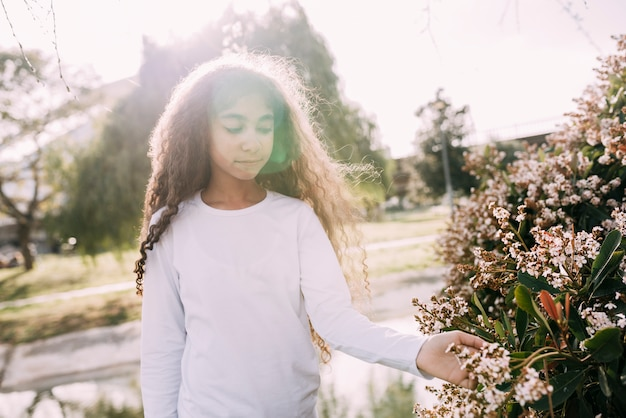 Petite fille jouant avec des fleurs dans le jardin