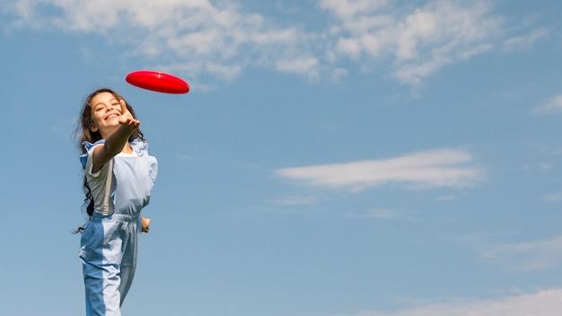 Petite fille jouant avec un frisbee