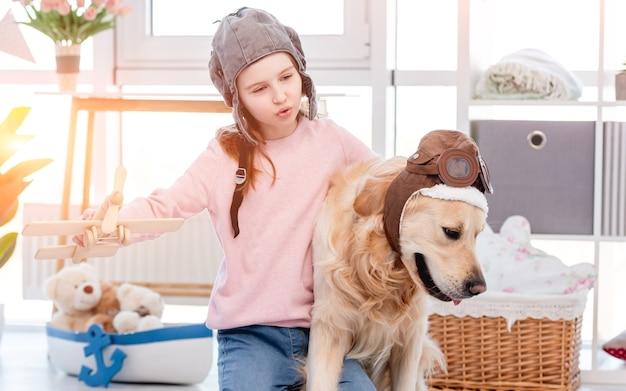 Petite fille jouant à des jeux de rôle en tant que pilote d'avion avec chien golden retriever