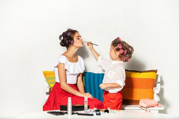Petite fille jouant avec le maquillage de sa maman