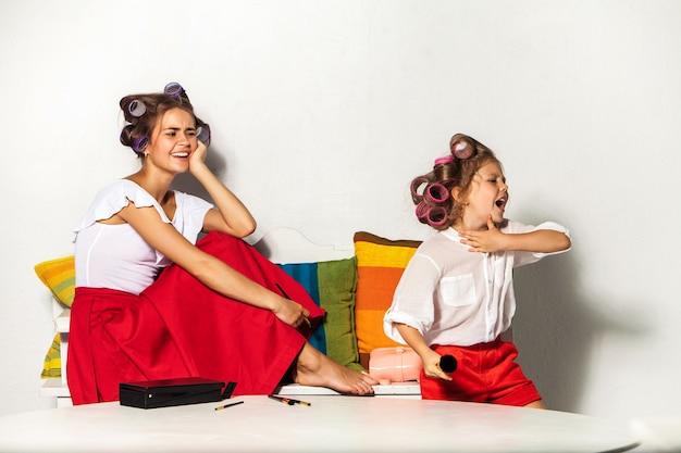 Petite fille jouant avec le maquillage de sa mère sur blanc