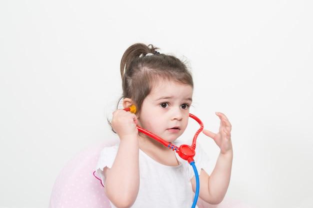 Petite fille jouant un médecin avec stéthoscope jouet sur fond blanc