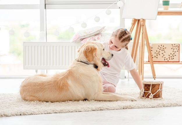 Petite fille jouant de la musique avec un chien