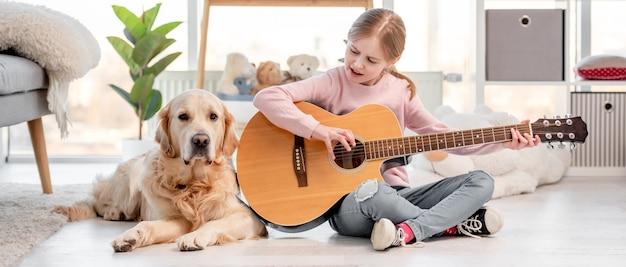 Petite fille jouant de la musique à la guitare et chien golden retriever couché à côté d'elle dans une pièce ensoleillée