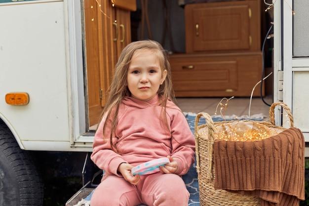 Petite fille jouant avec un nouveau jouet sensoriel tendance pop it sur les marches d'une caravane