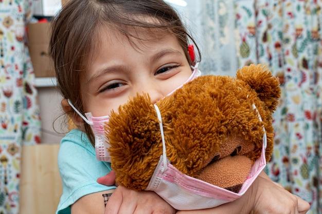 Petite fille jouant ours jouet dans un masque de protection médicale pendant l'isolement de quarantaine
