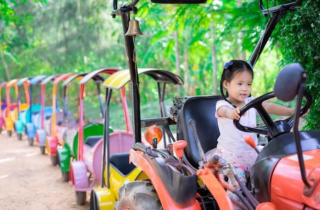 Petite fille jouant pour conduire un train