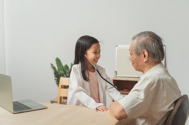 Petite-fille jouant pour être médecin à l'aide d'un stéthoscope vérifiant son grand-père