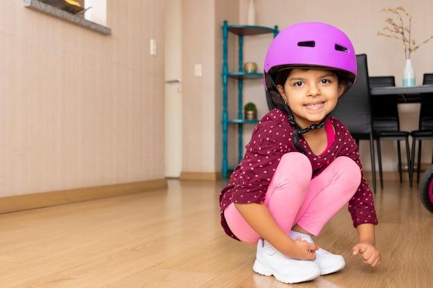 Petite fille jouant de son vélo dans le salon de l'appartement en quarantaine