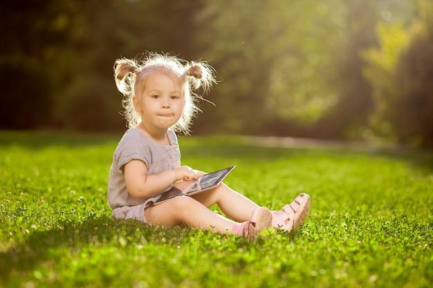 Petite fille jouant avec une tablette dans le parc