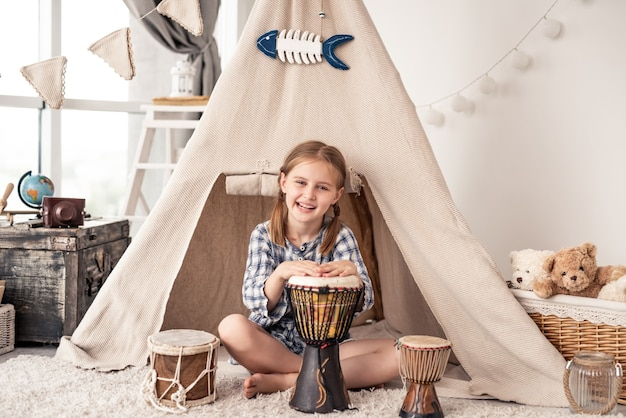 Petite fille jouant sur des tambours de djembé africains traditionnels assis en wigwam à la maison