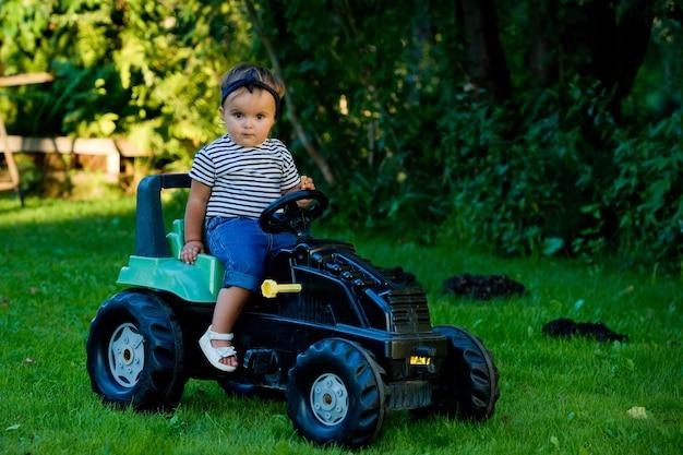 Petite fille jouant avec un tracteur jouet dans un jardin.