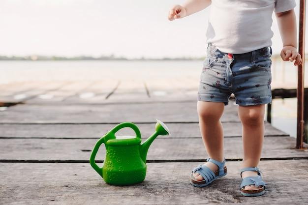 Une petite fille joue avec un arrosoir d'un pont en bois