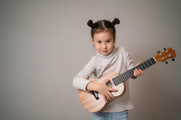 Une petite fille joue au développement créatif du ukulélé dans l'éducation musicale des enfants dès l'enfance en enseignant la musique en ligne à la maison