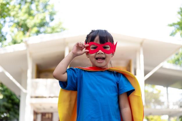La petite fille joue au super-héros. enfant sur fond blanc. concept de pouvoir de fille